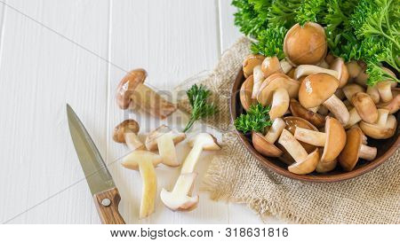 Mushrooms In A Clay Bowl On A Piece Of Burlap And A Knife On A White Table. Natural Vegetarian Cuisi