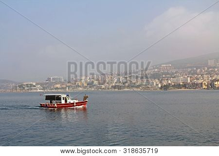 The Coastline Of The City Of Kusadasi, Turkey As Seen Across The Water On A Hazy Foggy Day With A Fi