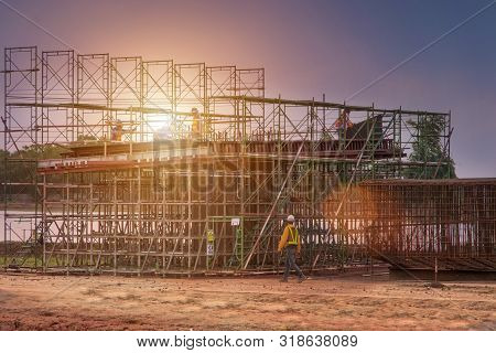 Man Working On Construction Site With Scaffold And Building With Sunset Background,scaffolding For C