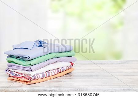 Stack Colorful Clothes. Pile Of Folded Cotton Shirts On A Bright Table With Space For Your Display P