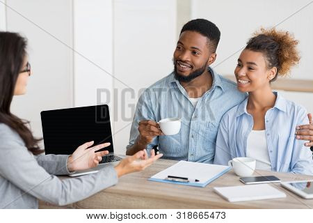 Happy Homebuyers. African American Spouses Having Consultation In Real Estate Agency. Selective Focu