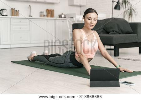 Jolly Female Watching Tablet During Home Workout Stock Photo