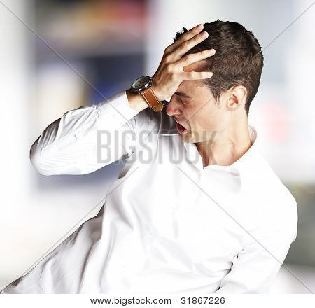 Angry young man doing frustration gesture indoor