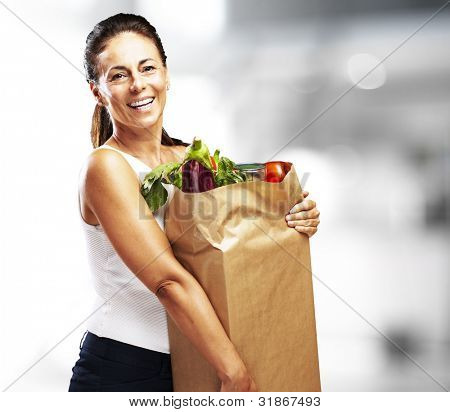 middle aged woman smiling and holding the purchase indoor