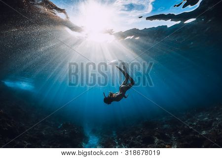 Free Diver Woman With Fins Over Coral Bottom And Amazing Sun Rays. Freediving Underwater In Ocean