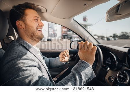 Happy Driver In A Suit Dancing In His Luxary Car Listening To Music And Enjouying Life. Concept Of S