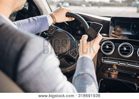 Young Businessman Looking At Mobile Phone While Driving A Car.