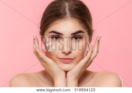 Beautiful Model Looks At The Camera While Moisturizing Cream With Hyaluronic Acid Is Applyed To Her