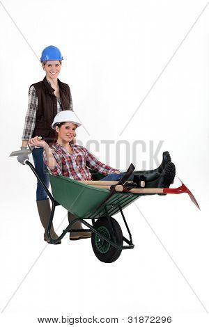 Female builder pushing colleague in wheelbarrow