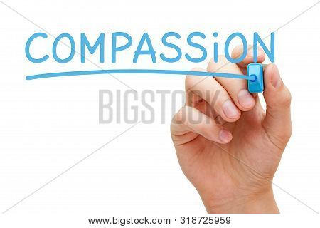 Hand Writing The Word Compassion With Blue Marker On Transparent Wipe Board Isolated On White.