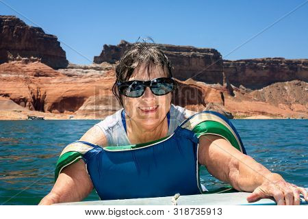 A Senior Woman With Sunglasses And A Big Smile Climbs Into The Back Of A Boat After Floating In Lake