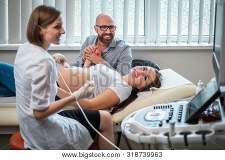 Pregnant woman and her husband on utltrasonographic examination at hospital