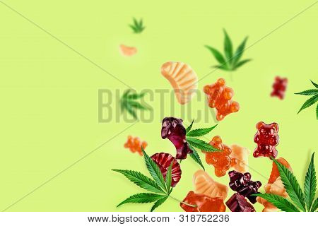 Colored Gummies Fly Along With Cannabis Leaves. Chewing Candies, Gummies With Cbd Oil And Thc. Color