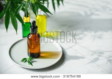 Cbd Oil Bottle And Dropper On A Small Plate And On A Marble Surface. Cannabis Leaves Nearby.