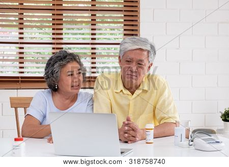 Asian Couple Seniors Use Laptop Video Conference With Doctor About Illness And Prescription Pill In