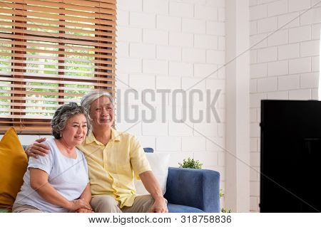 Asian Couple Senior Sitting On Sofa And  Watching Tv In Living Room At Home.panning From Blur Foregr
