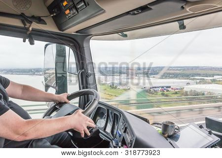 View Of Truck Driver In Interior Of Truck Cabin.the Truck Crosses The Queen Elizabeth Ii Bridge Over