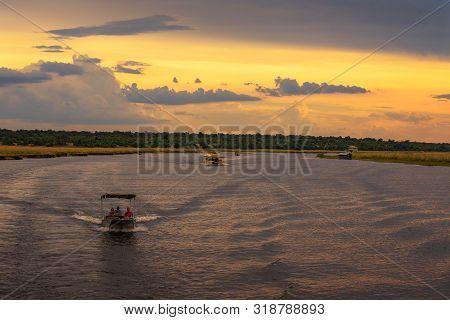 Chobe National Park, Botswana - April 7, 2019 : Boats With People On A Sunset Safari Cruise On Chobe