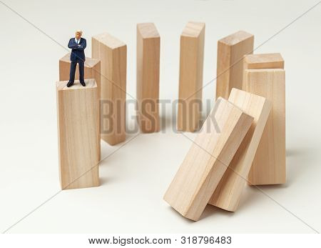 Karma Like Falling Dominoes. Businessman Pushed Dominoes And Expects And Analyzes The Result. Danger