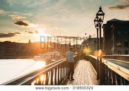 Stockholm, Sweden - June 27, 2019: Man Tourist Traveler Taking Pictures Photos Near Famous Skeppshol