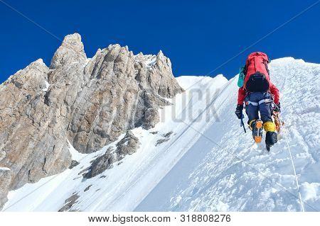 Climber Reaches The Summit Of Mountain Peak Enjoying The Landscape View.