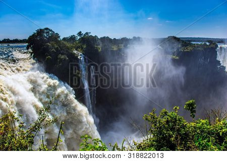 The waterfall is located on the Zambezi River. Giant cloud of water fog over the waterfall Victoria Falls. Journey after the wet season.