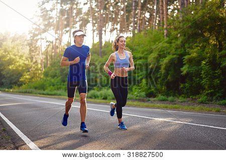 Fitness Sport Couple Running Jogging Outside Asphalt Road Pine Forest Nature Landscape. Runners Trai