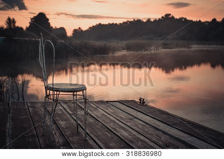 An Old Chair On A Pier With Beautiful Lake Views At Sunrise. Peaceful Toned Nature Background.