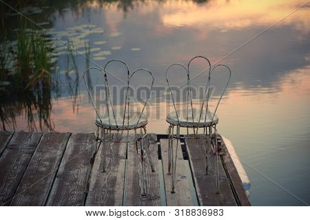 Two Old Chairs On The Edge Of The Pier Against The Backdrop Of The Lake, Which Reflects The Morning