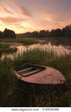 Boat In The Grass By The River. Dawn Over The River, Image In The Orange Toning.