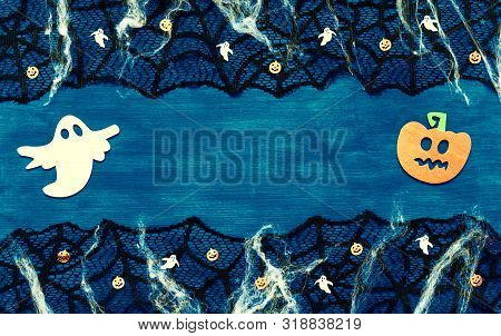 Halloween background - spider web, spiders and smiling jack and ghosts decorations as symbols of Halloween on the dark blue wooden background. Halloween concept