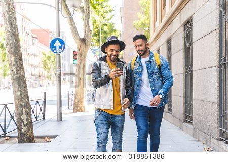 Two Male Friends Walking Together In The Street While Using Cell Phone.