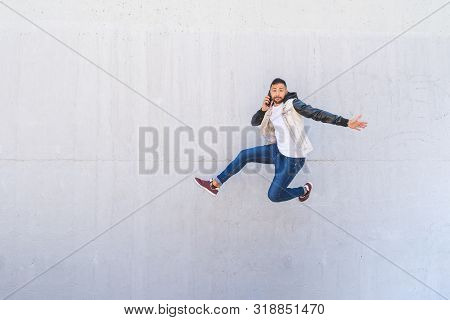 Latin American Man Jumping Excited On A Wall Background . Man Wearing A Hat Jumping In The Street. H