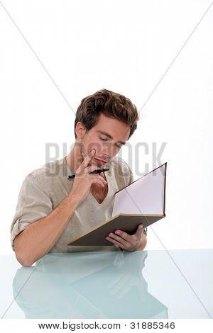 Pensive man writing in book