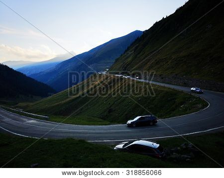 Mountains Shadows At The Sunset Time. Cars On The Transfagarasan Road, Fagaras Mountains. Nightscape
