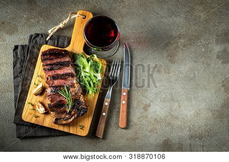 Grilled Ribeye Beef Steak With Red Wine, Herbs And Spices. Top View With Copy Space For Your Text. F