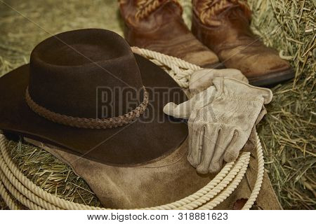 Western Lasso With A Cowboy Hat, Leather Gloves, Cowboy Boots And Leather Chaps On Hay With Shallow