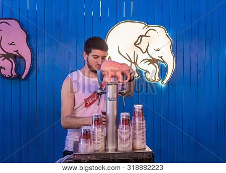 Nahariyya, Israel, August 22, 2019 : A Seller Near A Stand With Belgian Beer Delirium Pours Beer Int