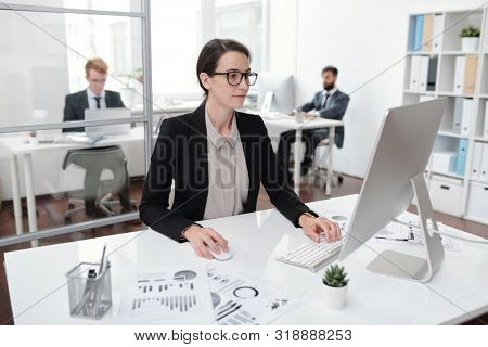 Portrait of young businesswoman wearing glasses using PC sitting at desk in office, accountant or manager concept