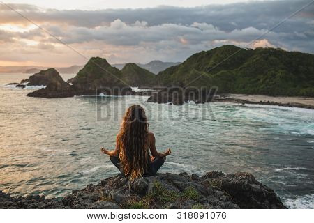 Young Woman Practicing Yoga In Lotus Pose At Sunset With Beautiful Ocean And Mountain View. Sensitiv