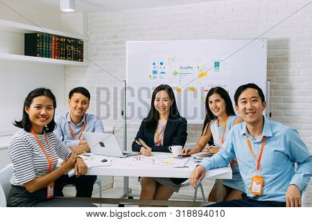Group Portrait Of Asian Business Men And Women Smiling And Looking At Camera At Company Meeting Room