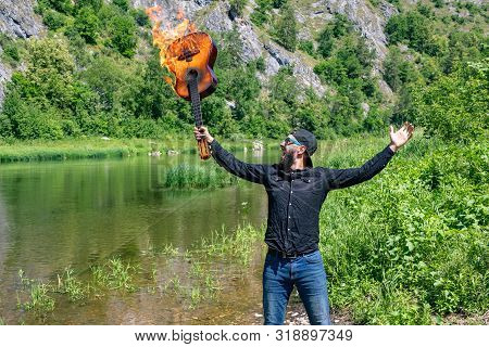 Young Bearded Rock Musician Screaming, Raised Up His Hands With A Burning Guitar. Against The Backdr