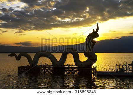 Sunset Beautiful And Silhouette Of Statue Dragon On Kwan Phayao, Phayao Province In Countryside,thai