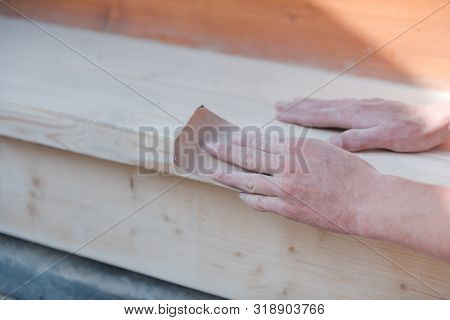 Sand the wood with sandpaper. A man polishes a tree. Work with sandpaper. To make wooden products. Make boards smooth. Joiner's works. poster
