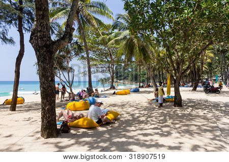 Phuket, Thailand - October 16th 2014: People Relaxing Under Trees On Surin Beach. This Is One Of The