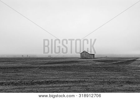 A Lonely Barn House Stands On The Early Autumn Fields Of The Rural Finland. The Mist Has Covered The