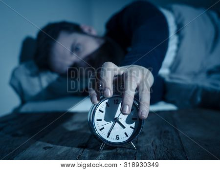 Desperate Stressed Young Man Whit Insomnia Lying In Bed Staring At Alarm Clock Trying To Sleep