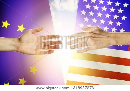 Two hands stretch towards each other against the background. Hands people against the backdrop flags European Union and USA poster