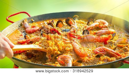 Paella traditional Spanish food, seafood paella in the fry pan with mussels, king prawns, langoustine and squids. Person Cooking paella outside, closeup