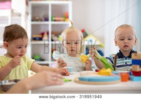 Group Of Babies Toddlers Playing At Table In Nursery Or Creche. Children In The Day Care Center. Fun